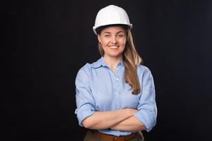 Photo of smiling young architect woman wearing white helmet over dark background
