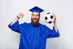 Amazed student man in bachelor celebrating and holding soccer ball photo