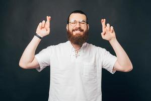 Photo of young bearded hipster man in white shirt crossing fingers and making a wish