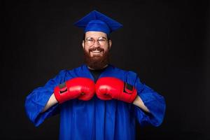 Photo of young man with beard in bachelor and using red boxing gloves