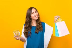 Charming young woman standing over yellow background and holding shopping bags and shopping trolley photo