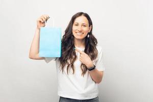 Foto de mujer hermosa alegre apuntando a la bolsa de papel azul