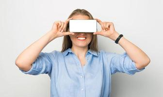 Photo of smiling business woman holding smartphone with white screen over eyes