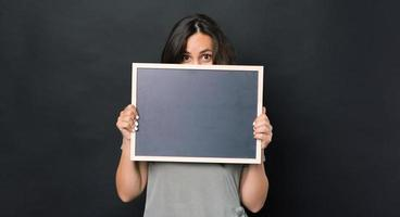 Photo of amazed woman holding black empty chalk board over dark background and covering face