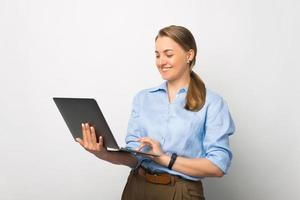 Photo of cheerful business woman using laptop over white background