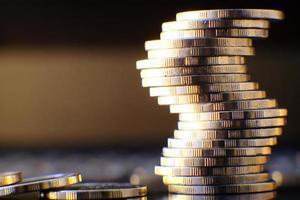 Monedas en el fondo de la tabla y ahorro de dinero y concepto de crecimiento empresarial, concepto de finanzas e inversión foto
