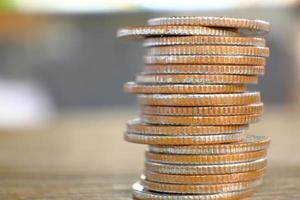Pila de monedas en el fondo de la tabla y ahorro de dinero y concepto de crecimiento empresarial, concepto de finanzas e inversión foto
