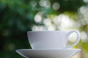 taza de café en el fondo de la mesa y café por la mañana foto