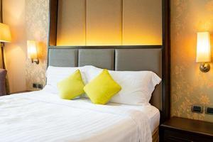 Cómoda decoración de almohadas en la cama en la habitación del hotel. foto