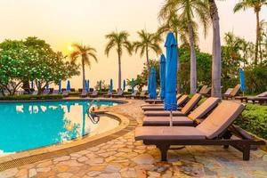 Beach chairs or pool beds with umbrellas around swimming pool at sunset time photo