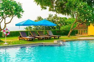 sillas de playa o tumbonas con sombrillas alrededor de la piscina al atardecer foto