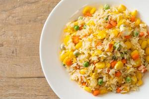 Homemade fried rice with mixed vegetables of carrots, green bean peas, corn, and egg photo