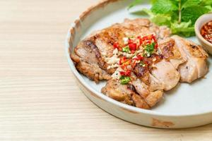 Savory grilled chicken with chili and garlic on a plate photo