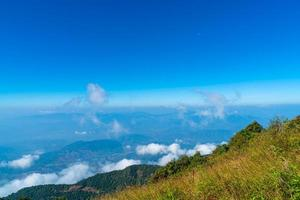 Beautiful mountain layer with clouds and blue sky at Kew Mae Pan Nature Trail in Chiang Mai, Thailand photo