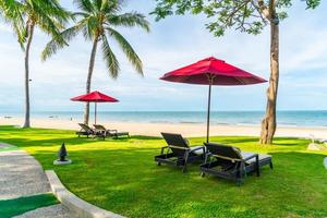 Umbrella and chairs with sea ocean view in hotel resort for holiday vacation travel concept photo