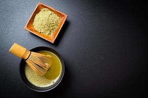 Hot matcha green tea cup with green tea powder and bamboo whisk photo