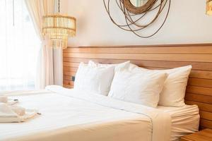 White pillow decoration on bed in bedroom interior photo