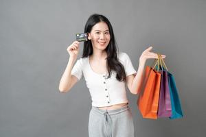 Young Asian woman hand holding shopping bag and credit card on grey background photo