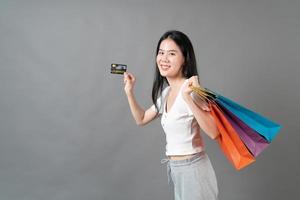 Joven mujer asiática mano sujetando una bolsa de compras y una tarjeta de crédito sobre fondo gris foto