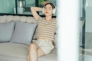 mujer sentada en el sofá escuchando música foto