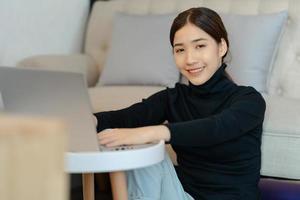 hermosa mujer asiática sentada en la sala de estar foto