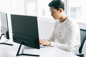Asian programmer focusing on his work photo