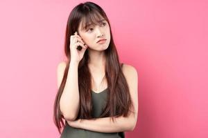 Young Asian girl posing on a pink background photo