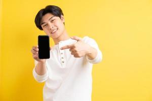 Asian man pointing at a phone photo