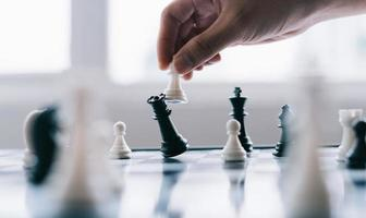 Asian businessman moving chess figure in competition photo