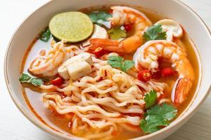 Instant noodles ramen in spicy soup with shrimps, or Tom Yum Kung - Asian food style photo