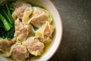 Pork wonton soup or pork dumpling soup with vegetables - Asian food style photo