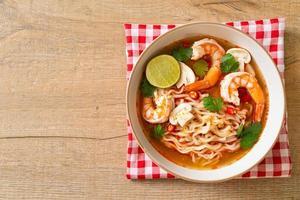 fideos instantáneos ramen en sopa picante con camarones, o tom yum kung - estilo de comida asiática foto