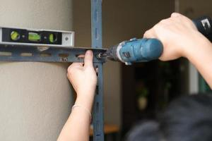 do it yourself concept, Craftsmen use electric drills to assemble old iron parts. Make a shelf on your free weekend photo