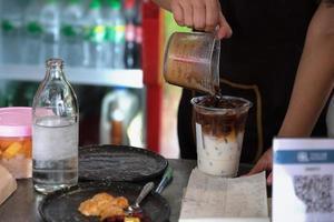 los empleados están poniendo café en vasos para preparar café con leche para los clientes. foto