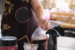 una empleada vierte café en un vaso de plástico para los clientes foto
