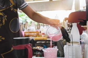 una empleada está vertiendo leche rosada en un vaso de plástico para los clientes foto