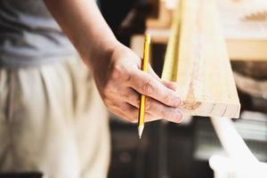 un carpintero mide los tablones para ensamblar las piezas y construir una mesa de madera para el cliente. foto