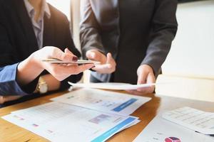 un auditor sostiene un bolígrafo apuntando a los documentos para examinar los presupuestos y el fraude financiero. foto