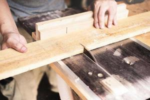 Los operadores de carpintería utilizan máquinas cortadoras de tablones para ensamblar y construir mesas de madera para los clientes. foto