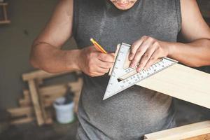un carpintero mide las placas para ensamblar las piezas. y construir una mesa de madera para los clientes. foto