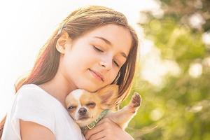 retrato de una niña, con su chihuahua. cachorro esponjoso. niña y un cachorro blanco. ternura, mascota. foto