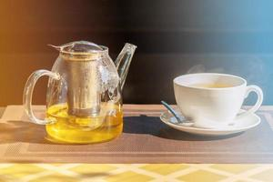 té de hierbas en una tetera de vidrio sobre la mesa al aire libre. té verde en una tetera y una taza. foto