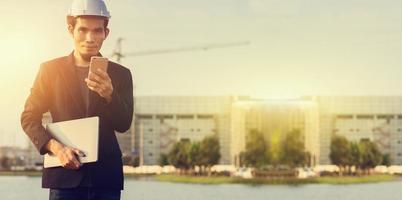 empresario usar casco de seguridad mediante teléfono móvil al aire libre sitio de construcción de fondo foto