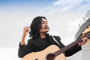 Man sing song and playing guitar outdoor photo