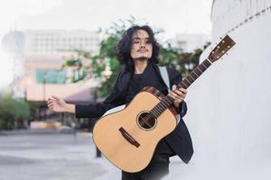 Asian man playing guitar music festival on street photo