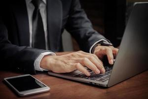 Close up hand using computer, Businessman typing laptop photo