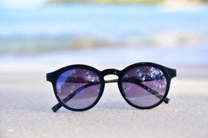 El cristal del sol está en la playa con vistas al mar de fondo, concepto de vacaciones de verano foto