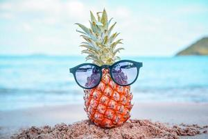 Pineapple And Sun Glasses On Beach st Sea Summer Background Concept photo