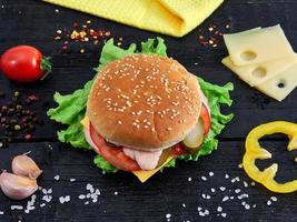 Tasty hamburger on wood background with vegetables and spices photo