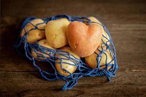 Patatas rojas en forma de corazón con patatas blancas en una eco-cuadrícula azul sobre un fondo de madera de cerca foto